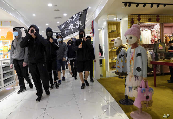 """Protesters carry a flag reading """"Liberate Hong Kong, the Revolution of Our Times"""" as they march through a shopping mall in Causeway Bay in Hong Kong, Dec. 26, 2019."""
