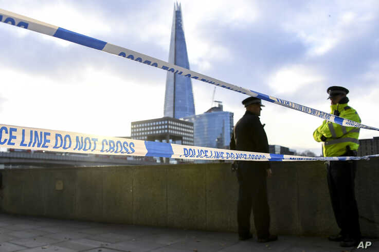 Police officers patrol the scene in central London, Dec. 1, 2019, after a knife attack on London Bridge.