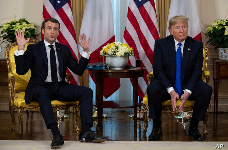 President Donald Trump, right, listens as French President Emmanuel Macron speaks at their meeting at Winfield House during the NATO summit, in London, Dec. 3, 2019.