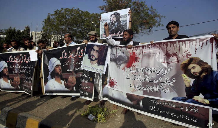 FILE - Supporters of Naqeebullah Mehsud, who was killed by police, hold a banner that reads