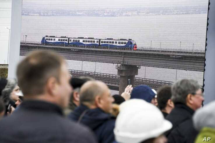 People watch a giant TV screen with Russian President Vladimir Putin, inside, riding a train across a bridge linking Russia and the Crimean peninsula in Taman, Russia, Dec. 23, 2019.