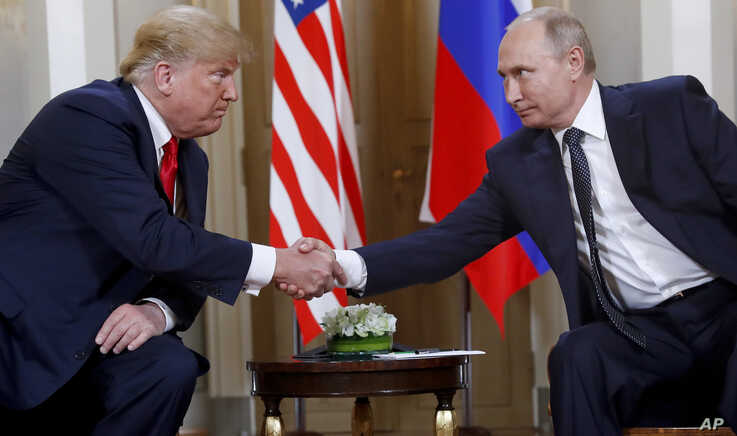 FILE - U.S. President Donald Trump, left, and Russian President Vladimir Putin shake hands at the beginning of a their bilateral meeting at the Presidential Palace in Helsinki, Finland, July 16, 2018.
