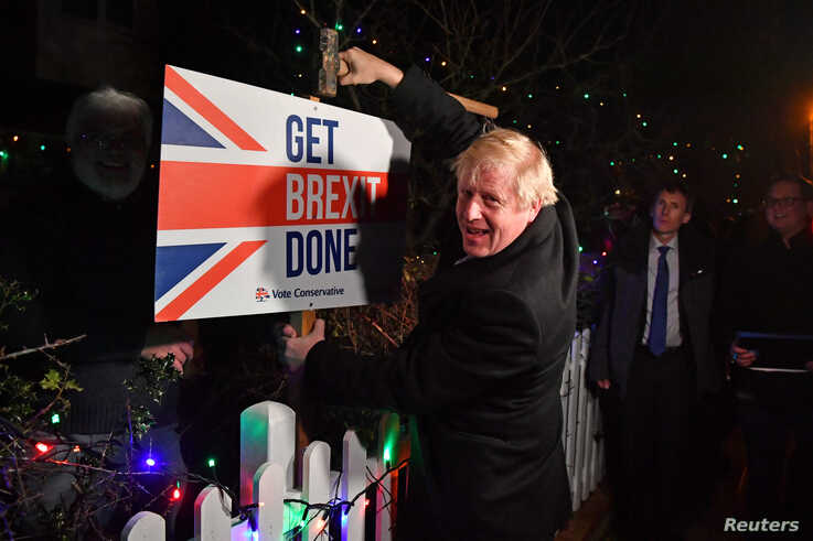 "FILE - Britain's Prime Minister and Conservative party leader Boris Johnson poses with a sledgehammer, after hammering a ""Get Brexit Done"" sign into the yard of a supporter, in South Benfleet, Britain, Dec. 11, 2019."