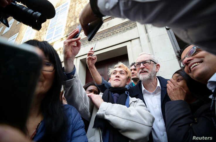 Britain's Labour Party leader and Prime Minister Boris Johnson's rival in the country's upcoming election Jeremy Corbyn takes pictures with people outside the University of London, in London, Britain, Dec. 3, 2019.