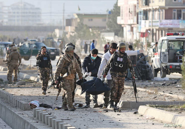 Afghan security forces carry a dead body after a blast in Kabul, Nov. 13, 2019.