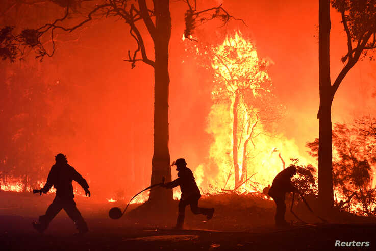 Rural Fire Service (RFS) volunteers and NSW Fire and Rescue officers fight a bushfire encroaching on properties near Termeil, Australia, Dec. 3, 2019.