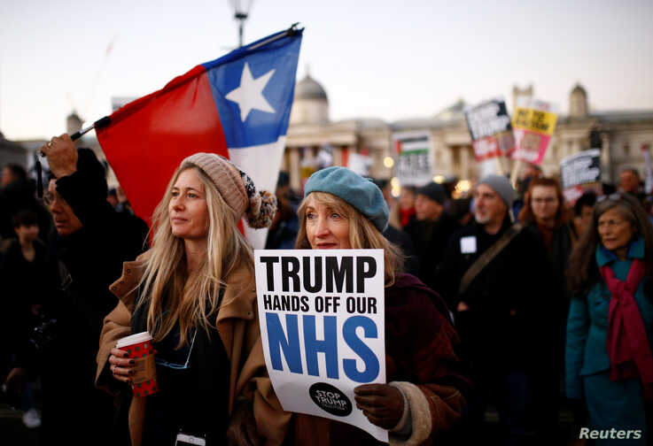 Protesters hold a placard at a demonstration during U.S. President Donald Trump's visit for NATO summit, in London, Dec. 3, 2019.