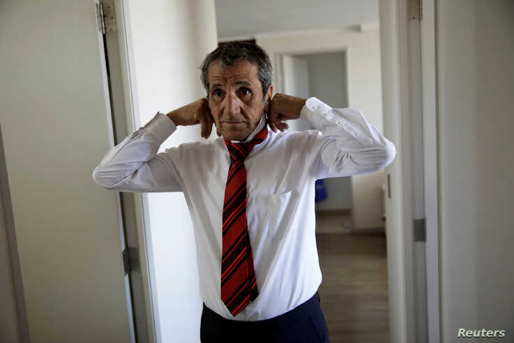 Gino Rojas gets dressed at his house in Santiago, Chile, Dec. 9, 2019.