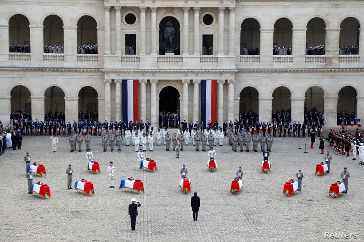 French President Emmanuel Macron pays his respect to the thirteen French soldiers killed in Mali, in front of the flag-draped coffins, during a ceremony at the Hotel National des Invalides in Paris.