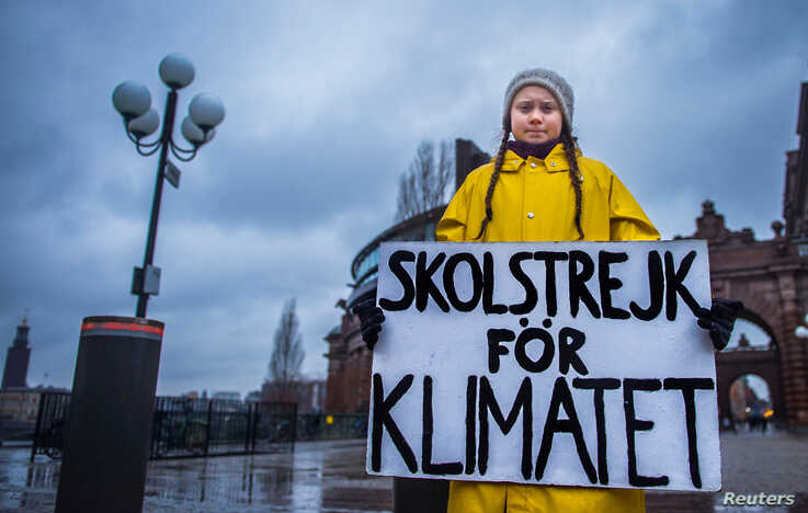 """FILE - Swedish girl Greta Thunberg, 15, holds a placard reading """"School strike for the climate"""" during a manifestation against climate change outside the Swedish parliament in Stockholm, Sweden, Nov. 30, 2018."""