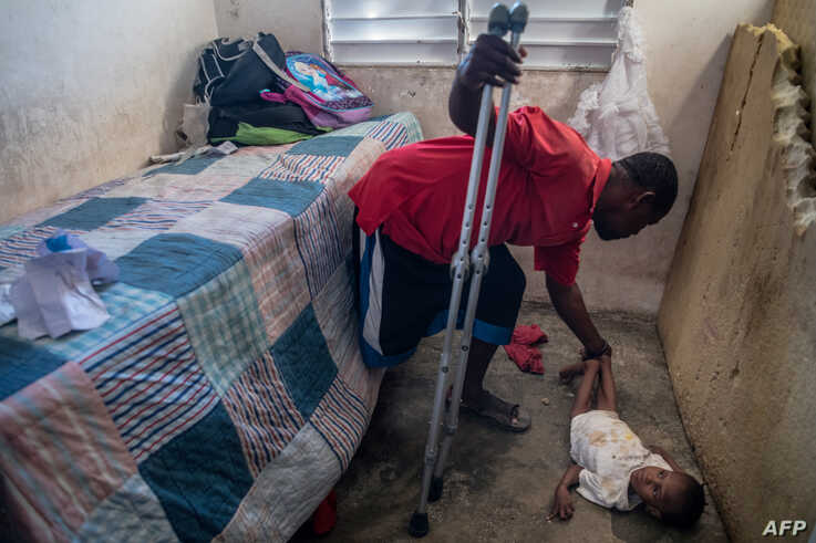 Boulva Verly, 34, tends to his son Woodyna Verly, 3, at their in Croix des Bouquets home, Jan. 2, 2020.