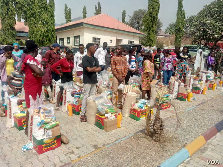 Widows and relatives of soldiers killed in battle stand behind food items they received from defense ministry authorities as part of a special remembrance event in Abuja, Nigeria, Jan. 11, 2020. (Timothy Obiezu/VOA)