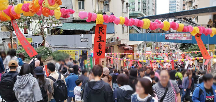 """Festive red strip of paper dangling in a Chinese new year market says: """"democracy and freedoms."""" (Photo: Verna Yu)"""