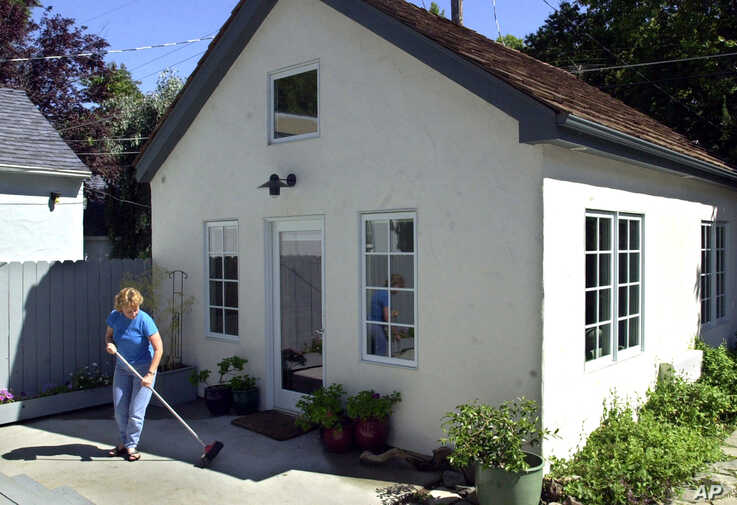 """FILE — Christine Minnehan sweeps up in front of her """"granny flat"""" located in the backyard of her Sacramento, California."""