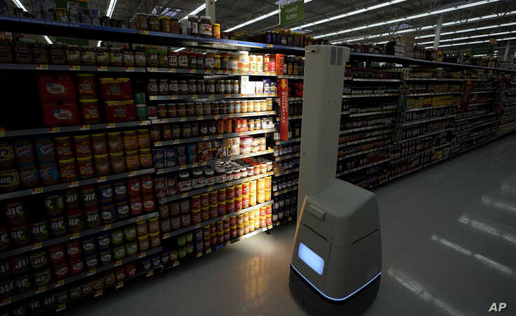 In this Nov. 9, 2018, photo, a robot scans shelves to provide real-time inventory data at a Walmart Supercenter in Houston.