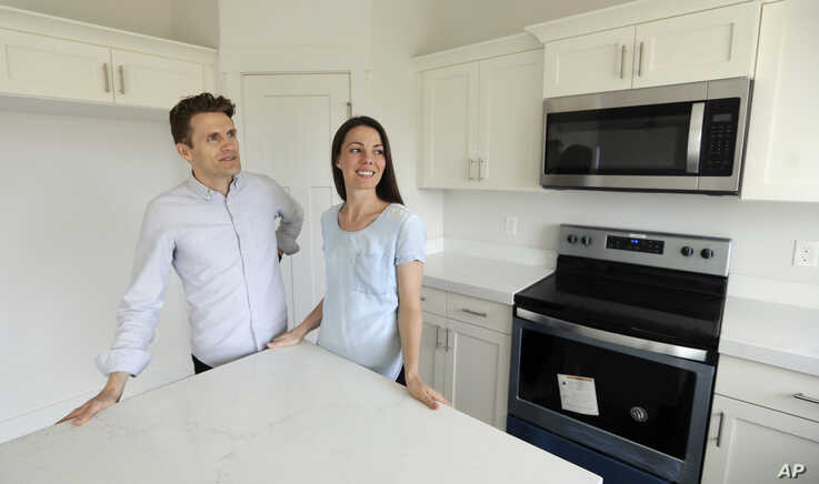 In this April 27, 2019, photo, millennials Andy and Stacie Proctor stand in their new home in Vineyard, Utah.