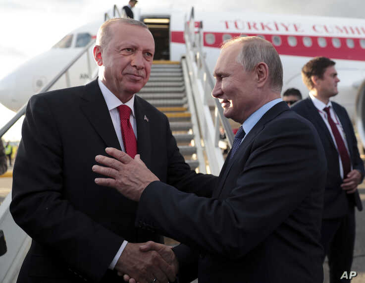 Russia's President Vladimir Putin, right shakes hands with Turkey's President Recep Tayyip Erdogan, prior to his departure from…