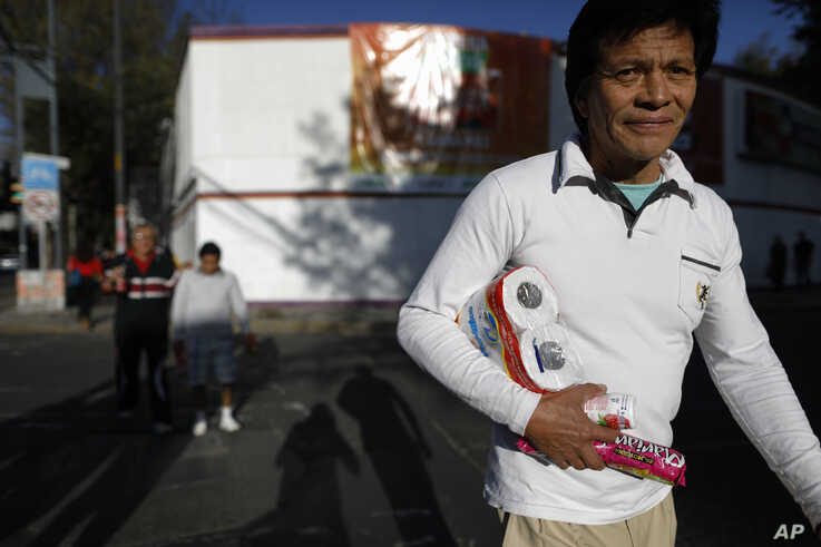 A man carries loose items after leaving a grocery store in Mexico City, Wednesday, Jan. 1, 2020. Stores stopped providing…