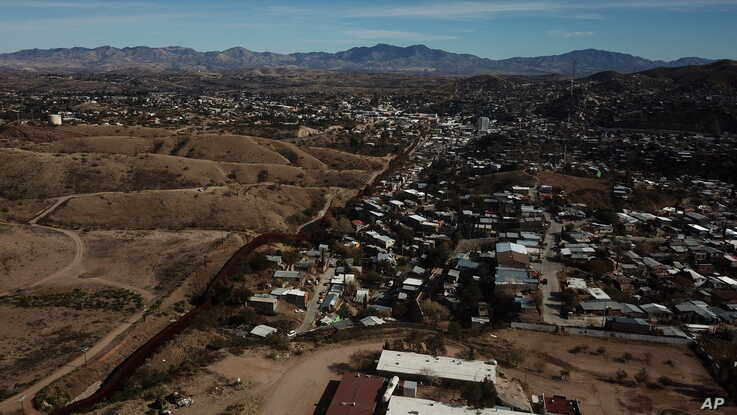 The U.S. border fence separates Nogales, Mexico, right, from sister city Nogales, Arizona, left, Jan. 3, 2020.