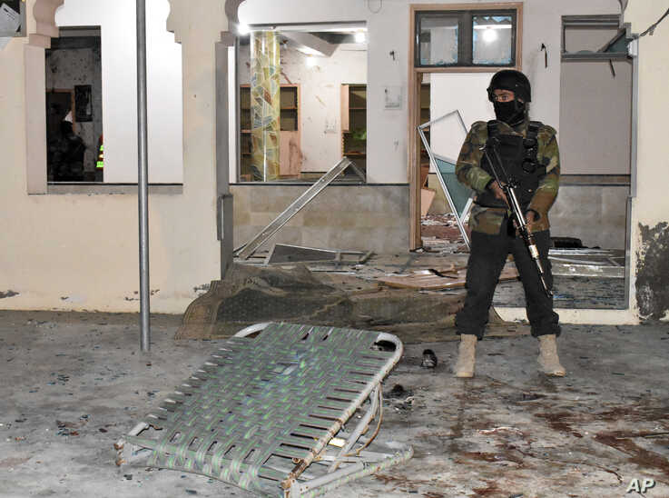 Pakistani police officer stands guard at the site of bomb explosion in a mosque in Quetta, Pakistan, Jan. 10, 2020.