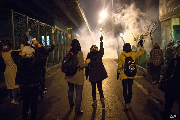 In this photograph taken Saturday, Jan. 11, 2020, protesters hold flowers as tear gas fired by police rises at a demonstration…