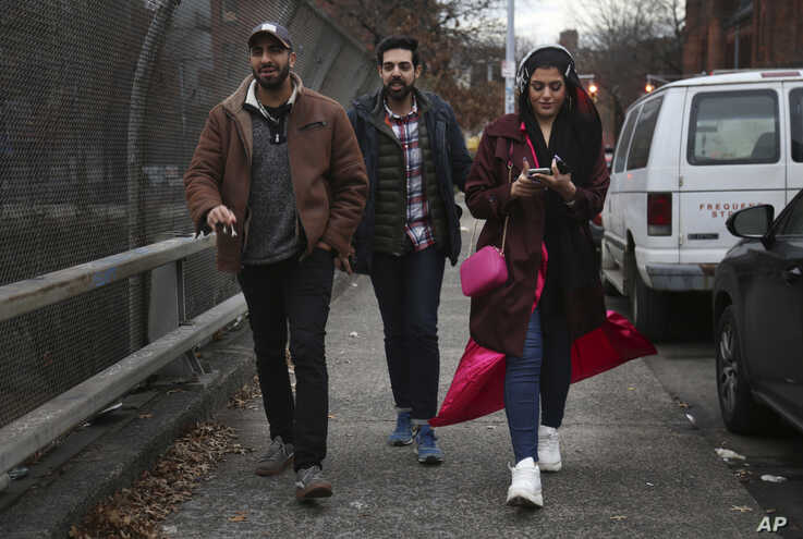 In this Dec. 27, 2019, photo, old college friends and acquaintances Mohammed Ali, left, of Stanton Island, and Saad Khan,…