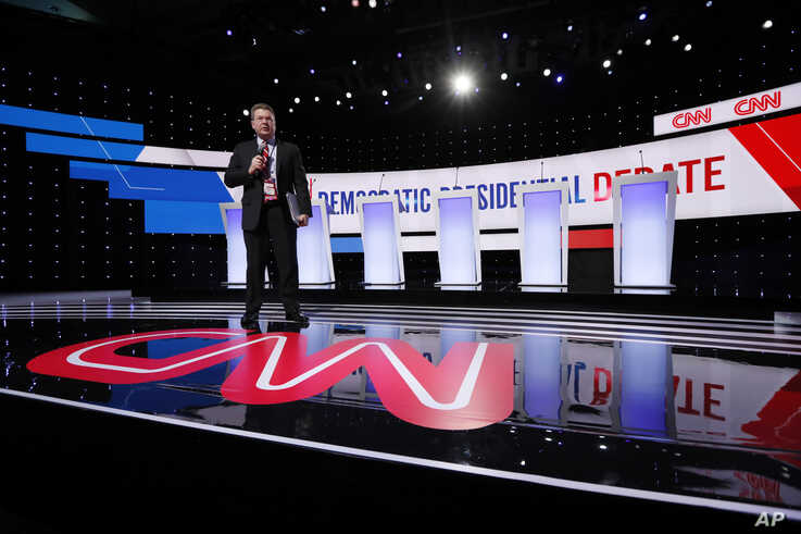 A CNN employee stands on the stage, Tuesday, Jan. 14, 2020, before a Democratic presidential primary debate hosted by CNN and…