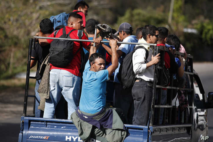 Honduran migrants get a ride on the back of a truck as they travel north in hopes of reaching the distant United States, in…