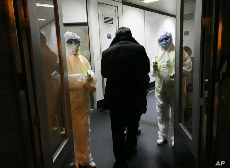 Health Officials in hazmat suits wait at the gate to check body temperatures of passengers arriving from the city of Wuhan…