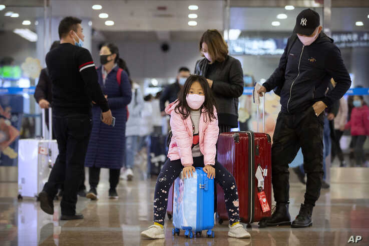 Travelers wear face masks as they stand in the arrivals area at Beijing Capital International Airport in Beijing, Jan. 23.
