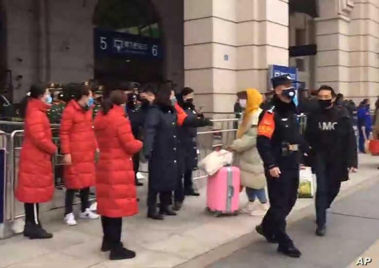 In this image made from video, security officials turn away a traveler at an entrance to the Hankou Railway Station in Wuhan in central China's Hubei Province, Jan. 23, 2020.