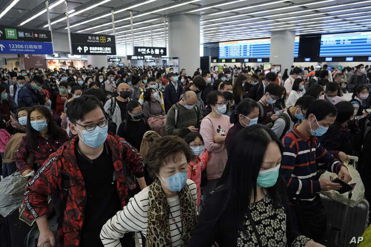 Passengers wear protective face masks at the departure hall of the high speed train station in Hong Kong, Jan. 23.
