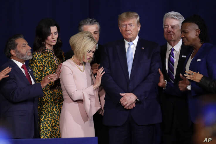 FILE - Faith leaders pray with President Donald Trump during a rally for evangelical supporters in Miami.