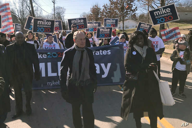 """Former New York City Mayor, and Democratic presidential candidate Michael Bloomberg walks with supporters along the route of the Little Rock """"marade"""" marking the Martin Luther King Jr. holiday in Little Rock, Arkansas, Jan. 20, 2020."""