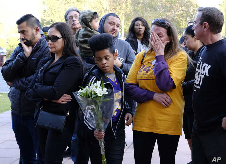 A Kobe Bryant fan brings flowers as other admirers grieve at a small memorial at the entrance of the Mamba Sports Academy
