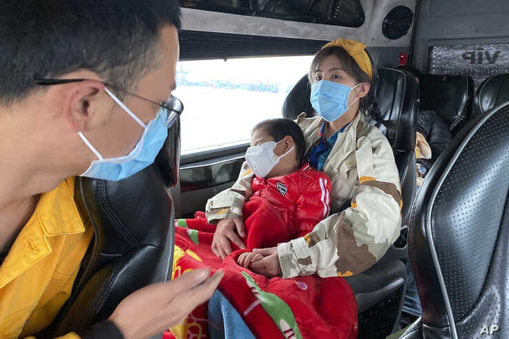 """People wear masks on a bus in Quang Ninh province, Vietnam, Jan. 28, 2018. A tourism company director in Vietnam says the coronavirus outbreak that began in China has hit his industry """"very hard, like a giant bomb."""""""