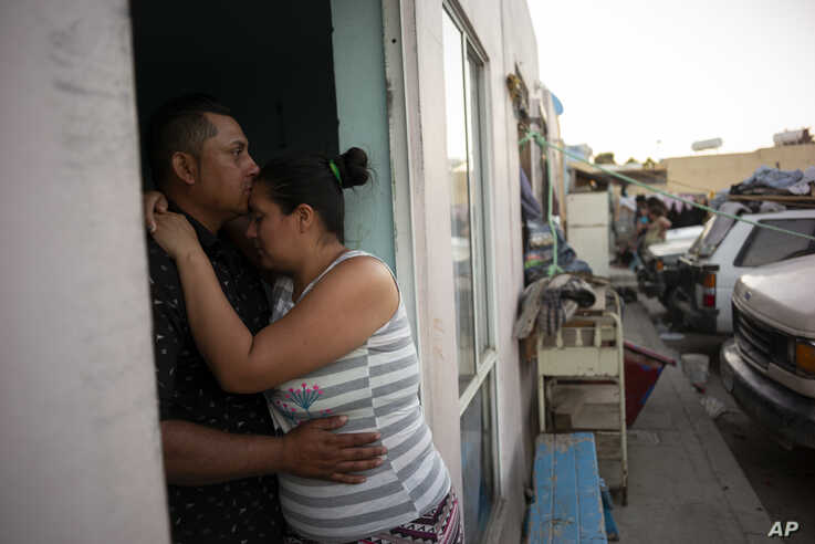 In this June 19, 2019, photo, Juan Carlos Perla, left, embraces his wife, Ruth Aracely Montoya in the entrance to their home in…