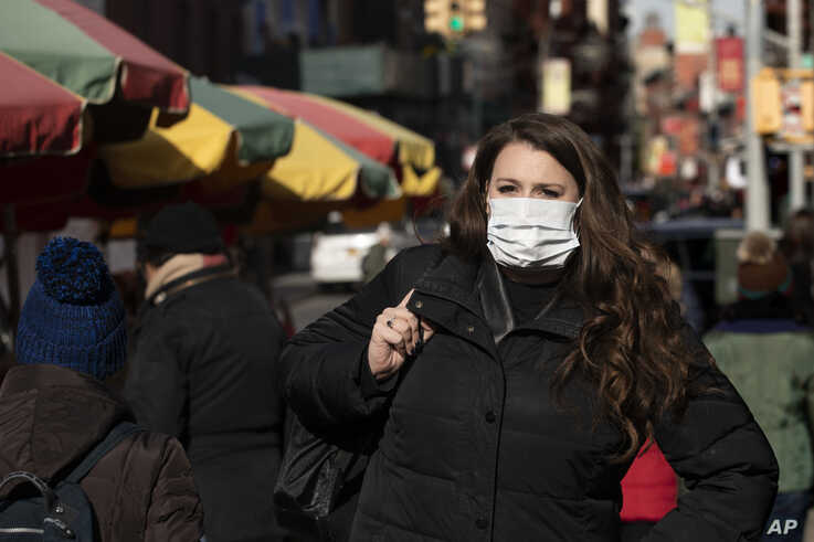 "A woman, who declined to give her name, wears a mask in New York, Jan. 30, 2020. She works for a pharmaceutical company and said she wears the mask out of concern for the coronavirus. ""I'd wear a mask if I were you,"" she said."