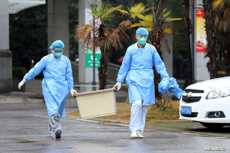 FILE - Medical staff carry a box as they walk at the Jinyintan hospital in Wuhan, China.