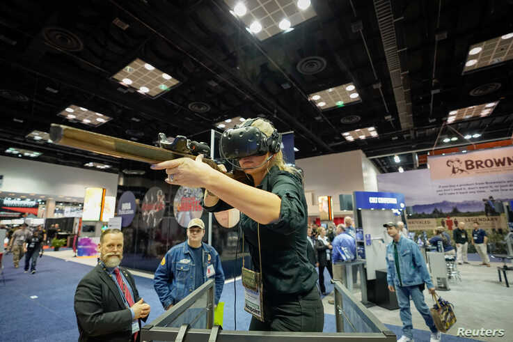 A woman uses a virtual reality based firearms simulator at the National Rifle Association's (NRA) annual meeting, in…