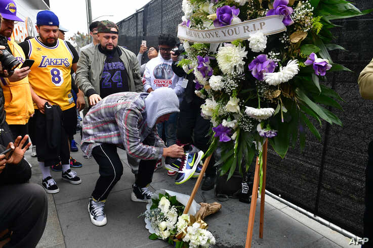 People gather around a makeshift memorial for former NBA and Los Angeles Lakers player Kobe Bryant after learning of his death, at LA Live plaza in front of Staples Center in Los Angeles, California, Jan. 26, 2020.