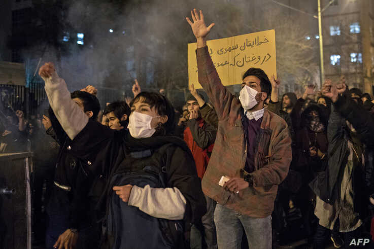 Protesters chant slogans and hold a placard reading in Farsi