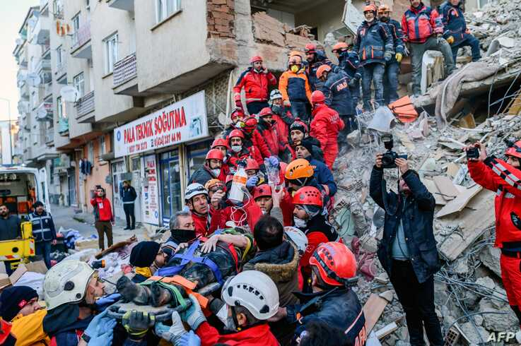 Rescue workers evacuate an injured woman from the rubble of a building after an earthquake in Elazig, eastern Turkey, Jan. 25, 2020.