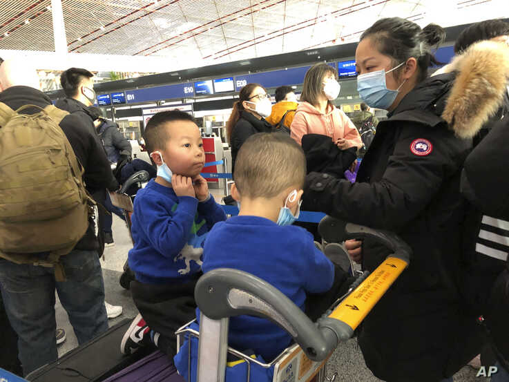 Children adjust their face masks as they and their mother wait in line at check-in counters at Beijing Capital International Airport, in Beijing, China, Jan. 25, 2020.