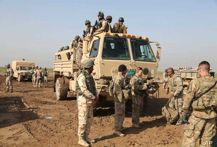 FILE - Iraqi soldiers participate in an exercise with American and Spanish trainers at Basmaya base, southeast of Baghdad, Iraq, Jan. 24, 2016.