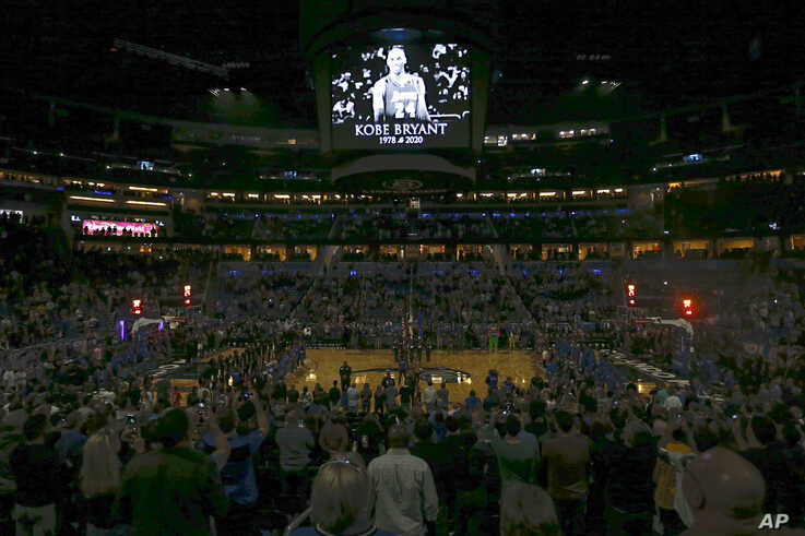 Fans stand for a moment of silence honoring Kobe Bryant before an NBA basketball game between the Orlando Magic and the LA Clippers in Orlando, Florida, Jan. 26, 2020.