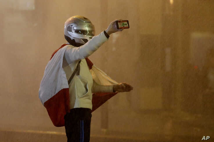 FILE - An anti-government protester is sprayed with a water cannon as he records video with his mobile phone during a protest in downtown Beirut, Lebanon, Jan. 22, 2020.