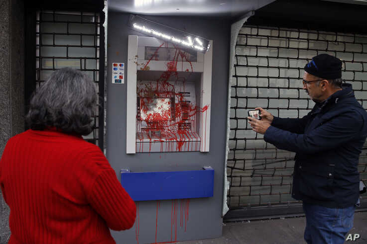 FILE - People use their phones to take pictures of an ATM machine damaged by anti-government protesters in Beirut, Lebanon, Jan. 15, 2020.