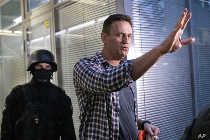 FILE - Russian opposition leader Alexei Navalny gestures as a security officer guards an entrance of his Anti-Corruption Foundation during a raid of its offices, in Moscow, Russia, Dec. 26, 2019.