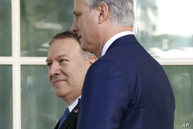 FILE - Secretary of State Mike Pompeo, back left, and National Security Adviser Robert O'Brien head to the Oval Office of the White House, in Washington, Nov. 25, 2019.
